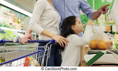 family weighing oranges on scale at grocery store -...