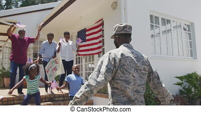 Rear view of an African American man enjoying time in the garden, with his family, wearing military uniform, returning home, with his multi-generation family greeting him, with his children running towards him, holding and waving american flags, on a sunny day, in slow motion