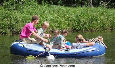 family with 4 kids in rubber boat, rowing