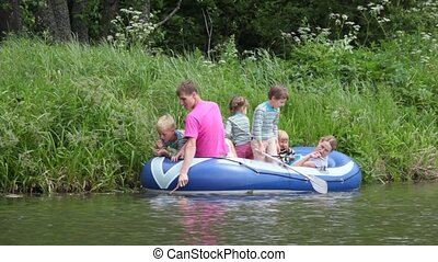family with 4 kids in rubber boat, fishing