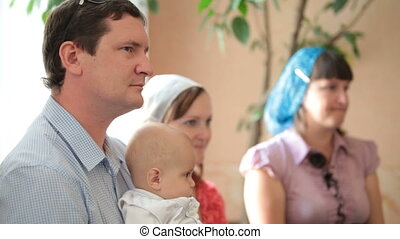 baptism in the church - family with a baby on the baptism in...