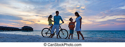 Family with a bike at tropical beach
