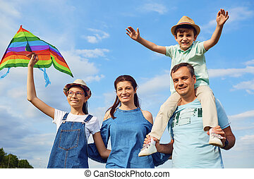 Family with a kite on the field in nature.