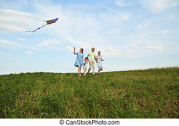 Family with a kite runs in nature.