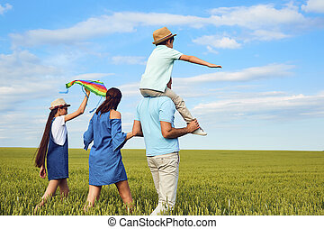 Family with a kite walking on the field in nature.