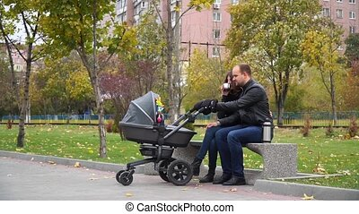 Family with a stroller on a bench in the park drinking tea