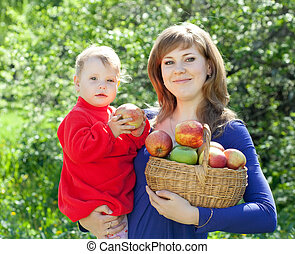 family with apples in orchard