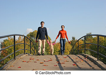 family with baby on autumn bridge