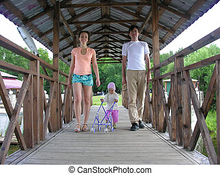 family with baby on bridge