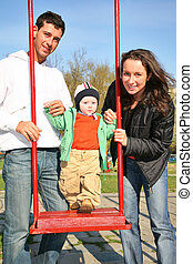 family with baby on seesaw