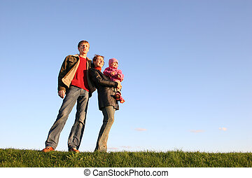 family with baby stand on grass