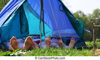 Family with bare feet lies in tent at forest on day, and then boy sits