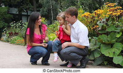 family with blow soap bubbles - Happy family with one little...