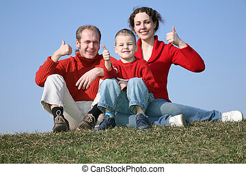 family with bou OK gesture on meadow