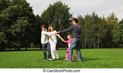 family with boy and girl drives a round dance on field in park