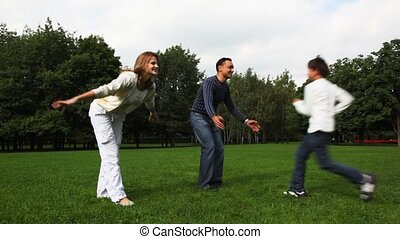 family with boy and girl embraces, kisses, turnes on field in park