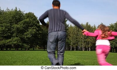 Family with boy and girl keeping for hands runs forward on park