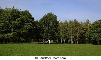 Family with boy and girl keeping for hands runs back on park