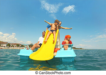family with boy and girl on pedal boat with yellow slide in...