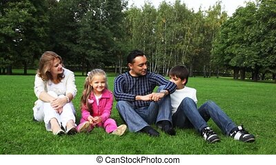 family with boy and girl sits in park on glass, looks against each other, talk and smiles