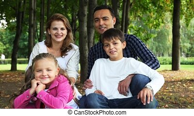 family with boy and girl sits in park and smiles