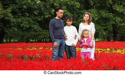 family with boy and girl stay in flowers in park talk and play