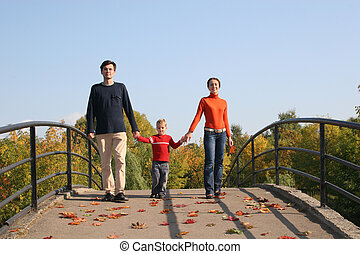family with boy on autumn bridge