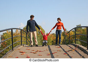 family with boy on bridge