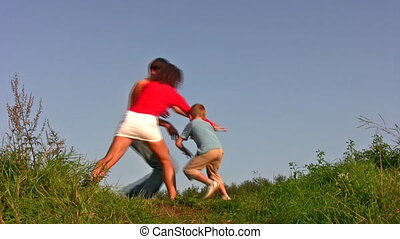 family with boy play tag on meadow