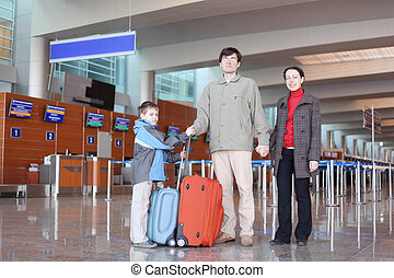 family with boy standing in airport hall with suitcases full body looking at camera