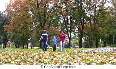 family with boy walking in park