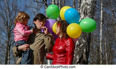family with bunch of balloons in forest - family of three...