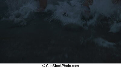 Family with child bathing in sea at twilight