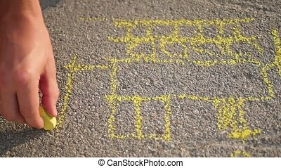 family with child draws with chalk on the asphalt. games outdoors