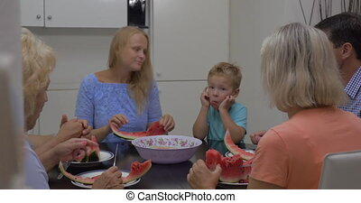 Family with child eating watermelon in the kitchen