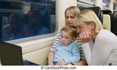 Family with child in the train watching video on laptop