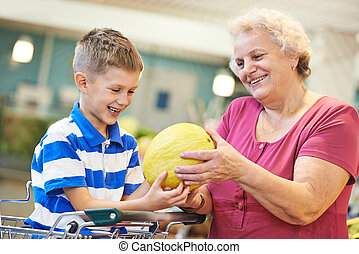 Family with child shopping fruits - Aged woman with man and...