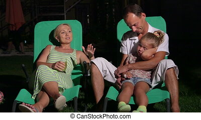 Family with child sitting on patio loungers in backyard of home at twilight