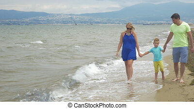 Family with child walking along the shore