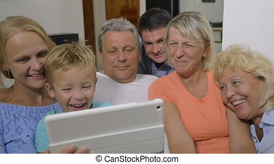 Family with child watching interesting video on pad