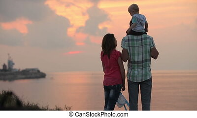 Family with child watching the sunset at the sea and embracing
