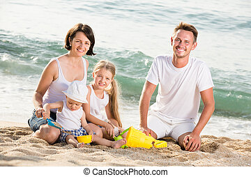 Family with children playing at beach