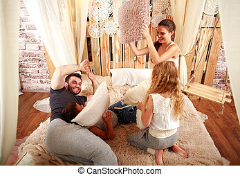 Family with children playing with pillows at home on bed