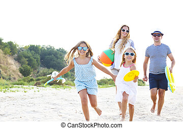 Family with children running at the beach