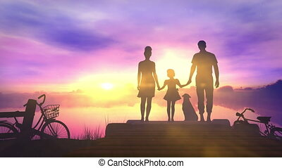 Family with children standing on a small pier admiring the sunset