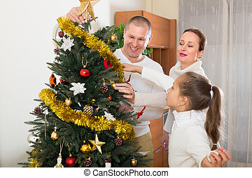 Family with Christmas tree at home
