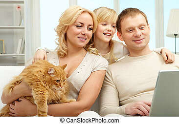 Family with computer - A family of three sitting on sofa and...