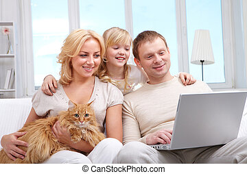 Family with computer - A family of three with cat sitting on...
