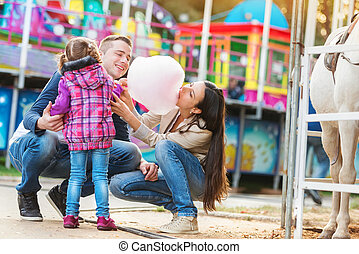 Family with daughter, amusement park, mother eating cotton...