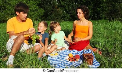 family with daughter and son rests in grass near forest and feeds each other fruit